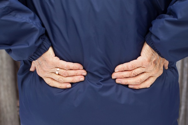 Elderly woman holding her back in pain with arthritis - Hosford Health Clinic