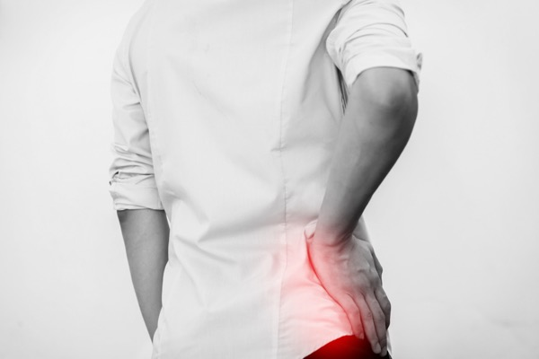 man holding his hip with hip pain - Hosford Health Clinic