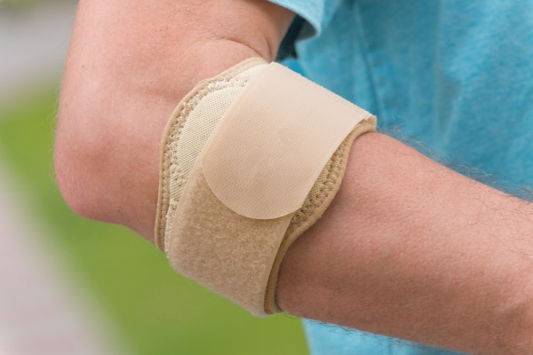 Sport injury treated by Hosford Health Clinic osteopath; man wearing tennis elbow brace