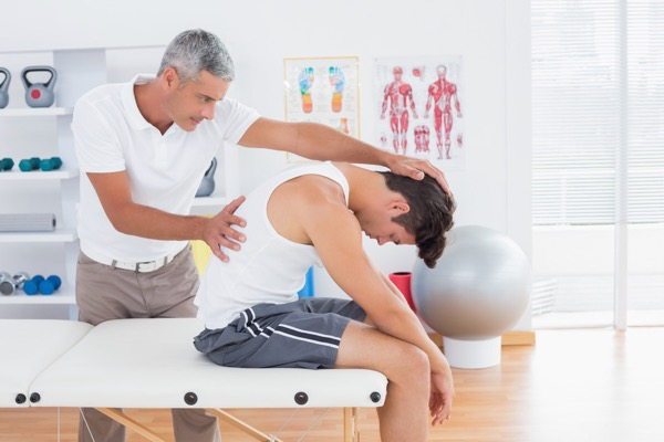 Osteopath examining the spinal alignment of a patient with neck with headache, neck and shoulder pain
