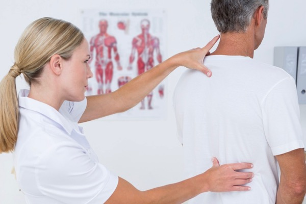 Osteopath examining a patient standing with headache, neck and shoulder pain