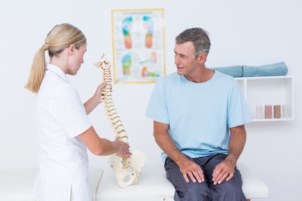 Hosford Health Clinic osteopath pointing at spine of male patient sitting