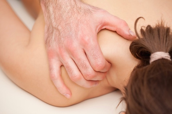 Osteopath treating a patient with headache, neck and shoulder pain