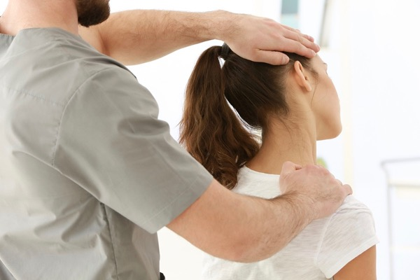 Osteopath stretching a patients neck with headache, neck and shoulder pain