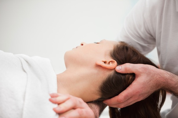 Osteopath stretching neck of patient with headache, neck and shoulder pain
