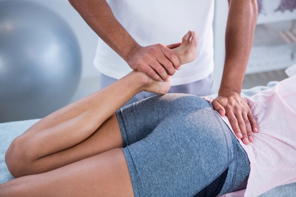 Hosford Health Clinic osteopath stretching quads of prone female patient