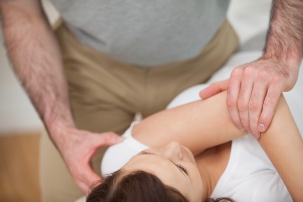 Osteopath treating a tight shoulder of a patient with headache, neck and shoulder pain
