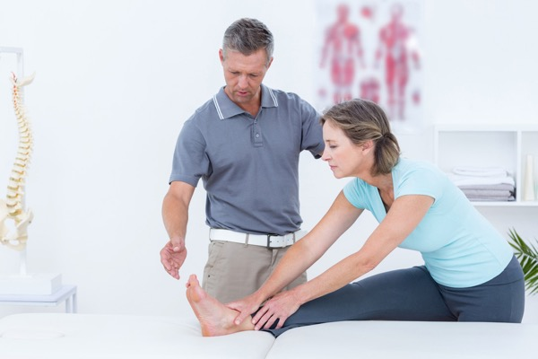 osteopath treating patient hamstring stretch