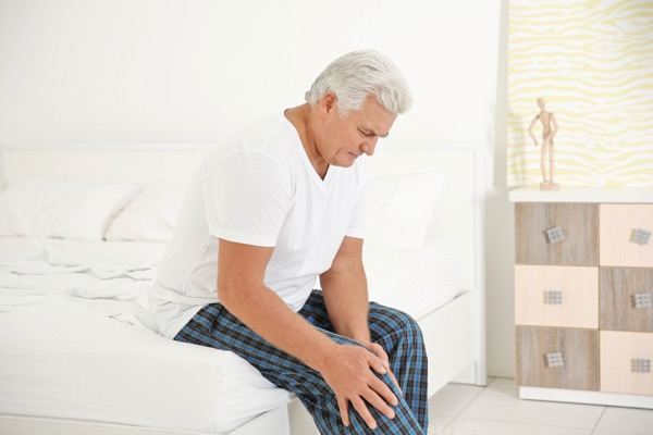 Senior man suffering from arthritis pain in his knee - Hosford Health Clinic